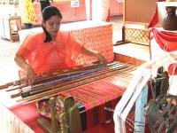Seorang Gadis bekerja dengan alat tenun secara manual
